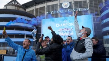 Manchester City fans celebrate outside the Etihad Stadium