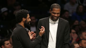 Kevin Durant (R) talking with Kyrie Irving (L) on the Nets' bench