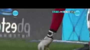 Belgrano keeper Juan Carlos Olave eat a cheeseburger thrown at him by Racing fans