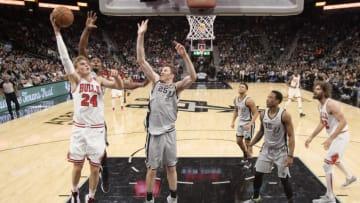 Dec 15, 2018; San Antonio, TX, USA; Chicago Bulls power forward Lauri Markkanen (24) shoots the ball over San Antonio Spurs small forward Dante Cunningham (behind) and Jakob Poeltl (25) during the first half at AT&T Center. (Soobum Im-USA TODAY Sports)