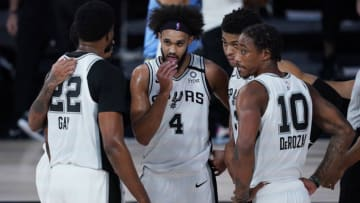 Aug 2, 2020; Lake Buena Vista, USA; San Antonio Spurs' Derrick White (4) confers with teammates Rudy Gay (22), DeMar DeRozan (10) and others during the second half of an NBA basketball game against the Memphis Grizzlies, Sunday, Aug. 2, 2020, in Lake Buena Vista, Fla. Mandatory Credit: Ashley Landis/Pool Photo via USA TODAY Sports