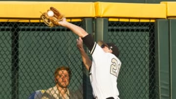 Jun 14, 2014; Omaha, NE, USA; Vanderbilt Commodores left fielder Bryan Reynolds (20) catches the fly ball at the fence against the Louisville Cardinals during game two of the 2014 College World Series at TD Ameritrade Park Omaha. Vanderbilt won 5-3. Mandatory Credit: Bruce Thorson-USA TODAY Sports