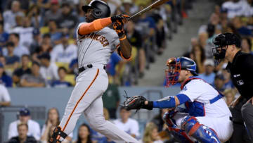 LOS ANGELES, CA - AUGUST 15: Andrew McCutchen #22 of the San Francisco Giants hits a three run homerun in front of Yasmani Grandal #9 of the Los Angeles Dodgers to tie the game 3-3 during the eighth inning at Dodger Stadium on August 15, 2018 in Los Angeles, California. (Photo by Harry How/Getty Images)