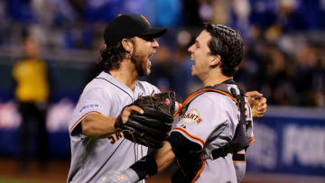 Buster Posey #28 and Madison Bumgarner #40 of the San Francisco Giants celebrate after defeating the Kansas City Royals to win Game Seven of the 2014 World Series by a score of 3-2 at Kauffman Stadium on October 29, 2014 in Kansas City, Missouri. (Photo by Elsa/Getty Images)