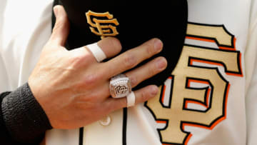 SAN FRANCISCO, CA - APRIL 07: Marco Scutaro #19 of the San Francisco Giants wears his 2012 Championship Ring and holds his hat during the playing of the National Anthem before their game against the St. Louis Cardinals at AT&T Park on April 7, 2013 in San Francisco, California. The Giants were given their Championship rings during a ceremony before the start of their game. (Photo by Ezra Shaw/Getty Images)