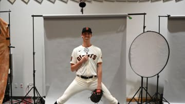 SF Giants pitcher Sean Hjelle (84), who is 6'11' helps out photographers so he so he fits in the seamless backdrop during spring training media day at Scottsdale Stadium. (Jayne Kamin-Oncea-USA TODAY Sports)