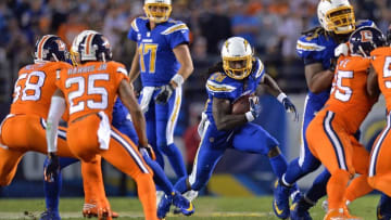 Oct 13, 2016; San Diego, CA, USA; San Diego Chargers running back Melvin Gordon (28) runs the ball after getting the hand off from quarterback Philip Rivers (17) as Denver Broncos cornerback Chris Harris (25) and outside linebacker Von Miller (58) defend during the third quarter at Qualcomm Stadium. Mandatory Credit: Jake Roth-USA TODAY Sports