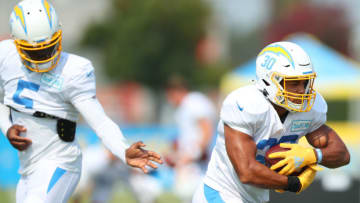 COSTA MESA, CALIFORNIA - AUGUST 20: Tyrod Taylor #5 of the Los Angeles Chargers hands the ball to Austin Ekeler #30 during the Los Angeles Chargers Training Camp at the Jack Hammett Sports Complex on August 20, 2020 in Costa Mesa, California. (Photo by Joe Scarnici/Getty Images)