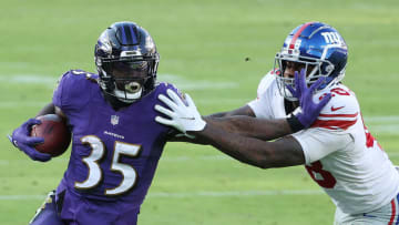 BALTIMORE, MARYLAND - DECEMBER 27: Running back Gus Edwards #35 of the Baltimore Ravens runs against linebacker Tae Crowder #48 of the New York Giants during the second half at M&T Bank Stadium on December 27, 2020 in Baltimore, Maryland. (Photo by Patrick Smith/Getty Images)