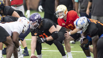 Jan 26, 2021; Mobile, Alabama, USA; National offensive lineman Quinn Meinerz of Wisconsin -Whitewater (71) gets set with National quarterback Ian Book of Notre Dame (12) in drills during National team practice during the 2021 Senior Bowl week. Mandatory Credit: Vasha Hunt-USA TODAY Sports