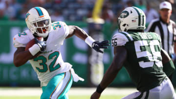 EAST RUTHERFORD, NJ - SEPTEMBER 24: Kenyan Drake #32 of the Miami Dolphins runs against Demario Davis #56 of the New York Jets during the second half of an NFL game at MetLife Stadium on September 24, 2017 in East Rutherford, New Jersey. The New York Jets defeated the Miami Dolphins 20-6. (Photo by Al Bello/Getty Images)