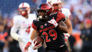 SAN DIEGO, CA - NOVEMBER 24: Rashaad Penny #20 of the San Diego State Aztecs eludes Bijon Parker #4 and DaQuan Baker #37 of the New Mexico Lobos for a rushing touchdown during the second half of a game at Qualcomm Stadium on November 24, 2017 in San Diego, California. (Photo by Sean M. Haffey/Getty Images)