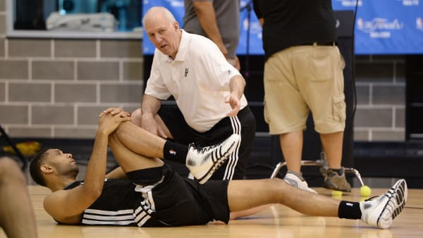 San Antonio Spurs head coach Gregg Popovich speaks with Tim Duncan while he stretches at the Spurs Practice Facility in San Antonio, Texas, June 7, 2014.  The Spurs defeated the Heat 110-95 in Game 1 of the NBA Finals on June 5.  NBA Finals Game 2 will take place in San Antonio on June 8.  AFP PHOTO / Robyn Beck        (Photo credit should read ROBYN BECK/AFP/Getty Images)