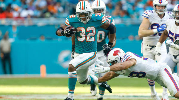 MIAMI, FL - DECEMBER 02:  Kenyan Drake #32 of the Miami Dolphins breaks a tackle from Matt Milano #58 of the Buffalo Bills during the first half at Hard Rock Stadium on December 2, 2018 in Miami, Florida.  (Photo by Michael Reaves/Getty Images)