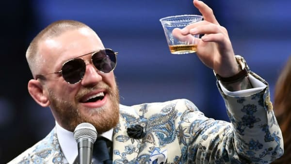 LAS VEGAS, NV - AUGUST 26:  Conor McGregor holds up a cup of his Notorious-branded Irish whiskey as he speaks during a news conference following his 10th-round TKO loss to Floyd Mayweather Jr. in their super welterweight boxing match at T-Mobile Arena on August 26, 2017 in Las Vegas, Nevada.  (Photo by Ethan Miller/Getty Images)
