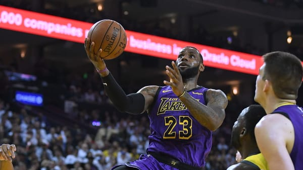 OAKLAND, CA - DECEMBER 25:  LeBron James #23 of the Los Angeles Lakers goes in for a layup over Draymond Green #23 of the Golden State Warriors during the first half of their NBA Basketball game at ORACLE Arena on December 25, 2018 in Oakland, California. NOTE TO USER: User expressly acknowledges and agrees that, by downloading and or using this photograph, User is consenting to the terms and conditions of the Getty Images License Agreement.  (Photo by Thearon W. Henderson/Getty Images)