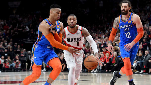 PORTLAND, OR - APRIL 14:  Russell Westbrook #0 of the Oklahoma City Thunder passes the ball past Damian Lillard #0 of the Portland Trail Blazers to Steven Adams #12 during the second half of the game at the Moda Center on April 14, 2019 in Portland, Oregon. The Blazers won 104-99. NOTE TO USER: User expressly acknowledges and agrees that, by downloading and or using this photograph, User is consenting to the terms and conditions of the Getty Images License Agreement. (Photo by Steve Dykes/Getty Images)