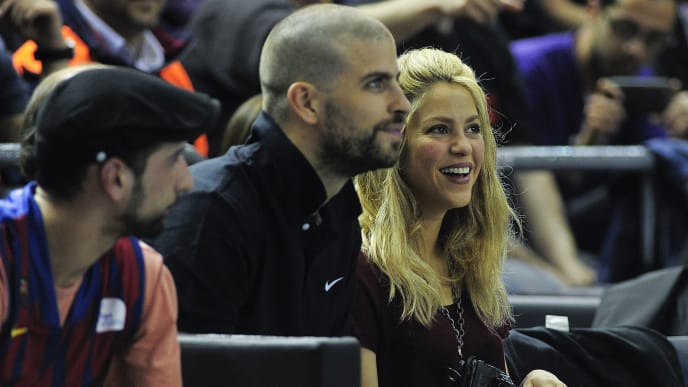 Barcelona's defender Gerard Pique (C) and his girlfriend Colombian's singer Shakira attend a Euroleague basketball playoffs match Regal FC Barcelona vs Panathinaikos at the Palau Blaugrana hall in Barcelona on April 25, 2013.     AFP PHOTO/ JOSEP LAGO        (Photo credit should read JOSEP LAGO/AFP/Getty Images)