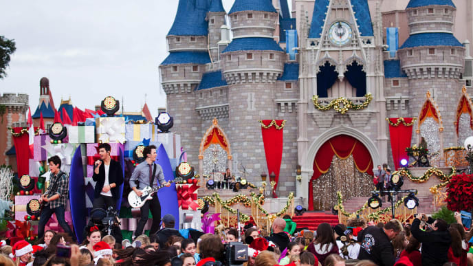 "LAKE BUENA VISTA, FL - DECEMBER 06:  In this handout photo provided by Disney,  The Jonas Brothers (L-R) Nick Jonas, Joe Jonas and Kevin Jonas perform in front of Cinderella Castle at the Magic Kingdom on December 6, 2009 in Lake Buena Vista, Florida.  The Jonas Brothers performed their new holiday single, ""Summertime Anthem,"" in a performance segment that was taped for the ""Disney Parks Christmas Day Parade."" The annual holiday telecast is scheduled to air on ABC-TV on December 25. (Photo by Matt Stroshane/Disney via Getty Images)"