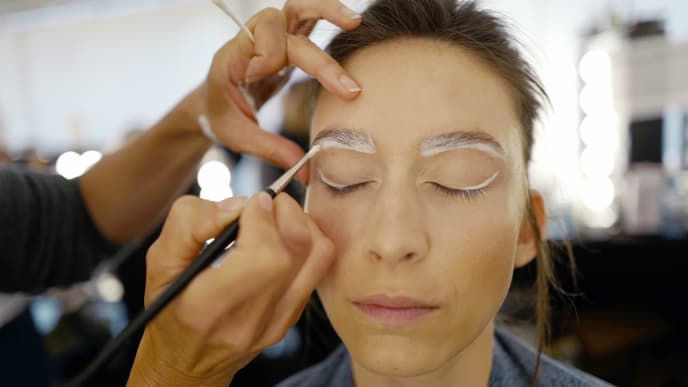 BERLIN, GERMANY - JULY 03: A model gets her makeup done backstage ahead of the Rebekka Ruetz show during the Berlin Fashion Week Spring/Summer 2020 at ewerk on July 03, 2019 in Berlin, Germany. (Photo by Joern Pollex/Getty Images for Rebekka Ruetz)