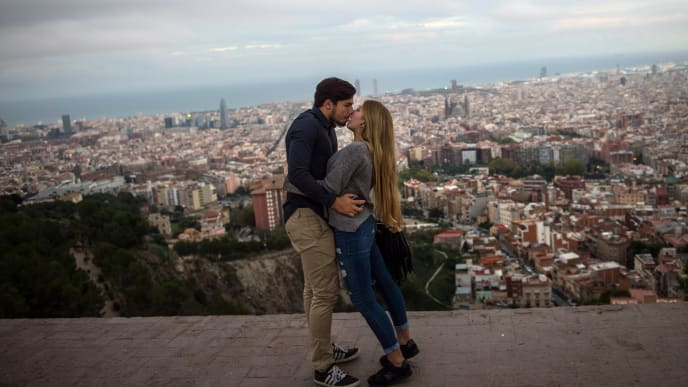 BARCELONA, SPAIN - OCTOBER 26: A couple of tourists kiss as they visit a former anti-aircraft bunker with the skyline of Barcelona in the background on October 26, 2015 in Barcelona, Spain. According to the last figures released by the Spain's Industry, Energy and Tourism Ministry, Spain has set a new tourist record with 54.4 million foreign visits up to September. (Photo by David Ramos/Getty Images)