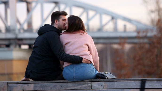 BERLIN, GERMANY - MARCH 11:  A couple kisses in a park on March 11, 2018 in Berlin, Germany. A high temperature of 16 degrees Celsius (61 degrees Fahrenheit) brought residents and tourists outside to enjoy the first day of spring weather of the year.  (Photo by Adam Berry/Getty Images)