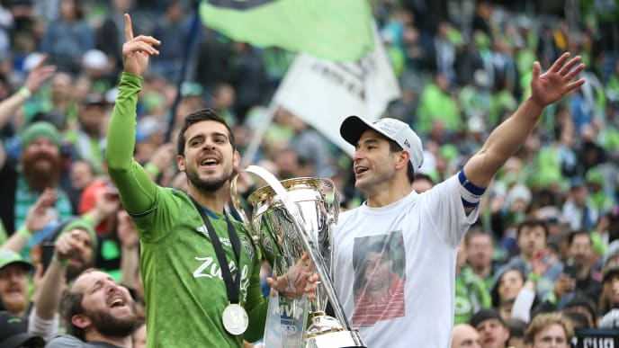 SEATTLE, WA - NOVEMBER 10: Victor Rodriguez #8 and Nicolas Lodeiro #10 of Seattle Sounders FC holds the trophy and celebrates after wining the match between Toronto FC and Seattle Sounders as part of the MLS Cup 2019 at CenturyLink Field on November 10, 2019 in Seattle, Washington. (Photo by Omar Vega/Getty Images)