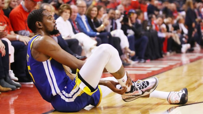 TORONTO, ONTARIO - JUNE 10:  Kevin Durant #35 of the Golden State Warriors reacts after sustaining an injury during the second quarter against the Toronto Raptors during Game Five of the 2019 NBA Finals at Scotiabank Arena on June 10, 2019 in Toronto, Canada. NOTE TO USER: User expressly acknowledges and agrees that, by downloading and or using this photograph, User is consenting to the terms and conditions of the Getty Images License Agreement. (Photo by Gregory Shamus/Getty Images)