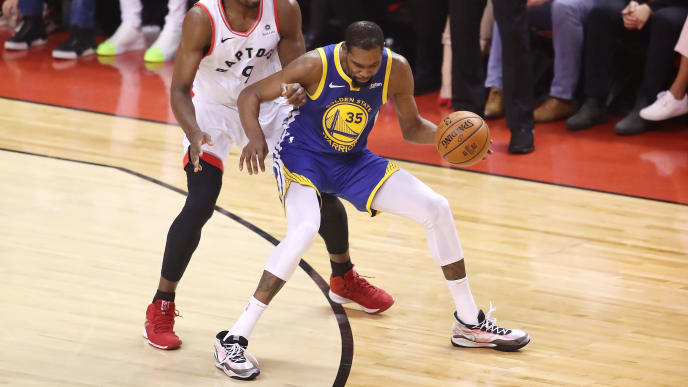 TORONTO, ONTARIO - JUNE 10:  Kevin Durant #35 of the Golden State Warriors sustains a leg injury while being defended by Serge Ibaka #9 of the Toronto Raptors in the second quarter during Game Five of the 2019 NBA Finals at Scotiabank Arena on June 10, 2019 in Toronto, Canada. NOTE TO USER: User expressly acknowledges and agrees that, by downloading and or using this photograph, User is consenting to the terms and conditions of the Getty Images License Agreement. (Photo by Claus Andersen/Getty Images)