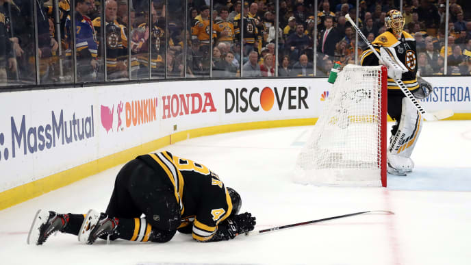 BOSTON, MASSACHUSETTS - MAY 29:  Matt Grzelcyk #48 of the Boston Bruins lays on the ice after being hit into the boards by Oskar Sundqvist (not pictured) #70 of the St. Louis Blues during the first period in Game Two of the 2019 NHL Stanley Cup Final at TD Garden on May 29, 2019 in Boston, Massachusetts. (Photo by Bruce Bennett/Getty Images)
