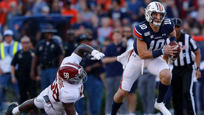 AUBURN, ALABAMA - NOVEMBER 30:  Bo Nix #10 of the Auburn Tigers breaks a tackle by Christian Barmore #58 of the Alabama Crimson Tide in the first half at Jordan Hare Stadium on November 30, 2019 in Auburn, Alabama. (Photo by Kevin C. Cox/Getty Images)
