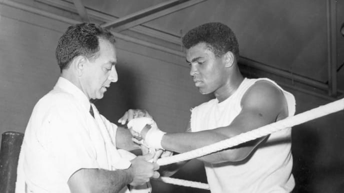 American boxer Muhammad Ali, the world heavyweight champion, has his hands bandaged by his manager Angelo Dundee before the day's training session at the Territorial Army Gymnasium at White City, London.  Ali is in training for his fight against the British champion Henry Cooper at Arsenal's Highbury Stadium, London on May 21st.  Original Publication: People Disc - HW0538   (Photo by Keystone/Getty Images)