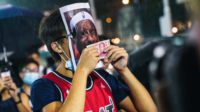 "HONG KONG, CHINA - OCTOBER 15: A basketball fan wearing Miami Heat jersey with a Lebron James mask on licking a 100 Chinese yuan bill on October 15, 2019 in Southorn Playground, Wan Chai, Hong Kong, China. Anti-government demonstrations in Hong Kong stretched into its fifth month after the Chinese territory's government invoked emergency powers earlier this month to introduce an anti-mask law. Protesters continue to call for Hong Kong's Chief Executive Carrie Lam to meet their remaining demands since the controversial extradition bill was withdrawn, which includes an independent inquiry into police brutality, the retraction of the word ""riot"" to describe the rallies, and genuine universal suffrage as the territory faces a leadership crisis. (Photo by Lampson Yip - Clicks Images/Getty Images)"