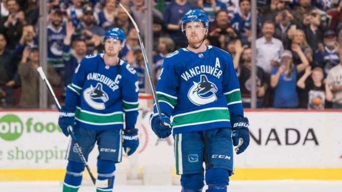 VANCOUVER, BC - OCTOBER 5: Daniel Sedin #22 and Henrik Sedin #33 of the Vancouver Canucks salute the fans after playing in their final home game of their career against the Arizona Coyotes in NHL action on April, 5, 2018 at Rogers Arena in Vancouver, British Columbia, Canada.  (Photo by Rich Lam/Getty Images)