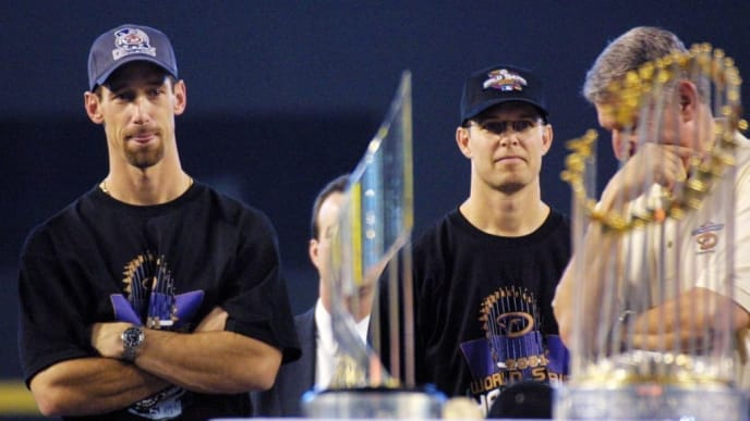 PHOENIX, AZ - NOVEMBER 7:  Arizona Diamondbacks' Luis Gonzalez (L), Jay Bell (C) and managing general partner Jerry Colangelo (R) attend a victory rally 07 November 2001 at Bank One Ballpark in Phoenix, AZ. In the foreground is the World Series trophy (R) and the MVP trophy presented to Diamondbacks' Randy Johnson and Curt Schilling. Gonzalez hit the winning RBI and Bell scored the winning run in game seven against the New York Yankees to win the 2001 World Series.  (Photo credit should read MIKE FIALA/AFP via Getty Images)