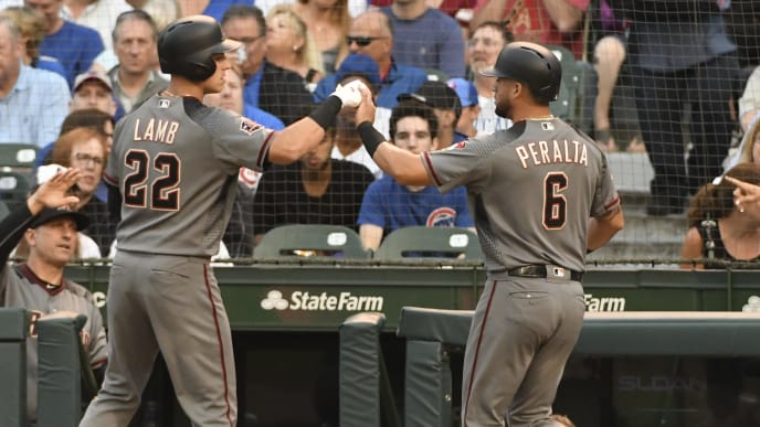 CHICAGO, IL - JULY 23: Jake Lamb #22 of the Arizona Diamondbacks greets David Peralta #6 after Peralta scored against the Chicago Cubs during the first inning on July 23, 2018 at Wrigley Field in Chicago, Illinois.  (Photo by David Banks/Getty Images)