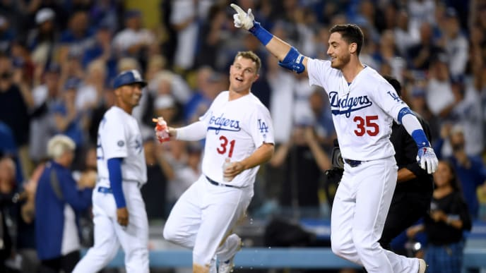 LOS ANGELES, CALIFORNIA - JULY 03:  Cody Bellinger #35 of the Los Angeles Dodgers celebrates his walk off solo homerun in front of Joc Pederson #31 and third base coach Dino Ebel #12, for a 5-4 win over the Arizona Diamondbacks, during the tenth inning at Dodger Stadium on July 03, 2019 in Los Angeles, California. (Photo by Harry How/Getty Images)