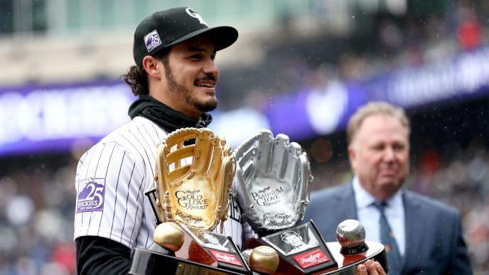 DENVER, CO - APRIL 06:  Nolan Arenado of the Colorado Rockies receives the Rawlings Gold Glove and Platinum Glove Award before the Rockies home opener against the Atlanta Braves at Coors Field on April 6, 2018 in Denver, Colorado.  (Photo by Matthew Stockman/Getty Images)