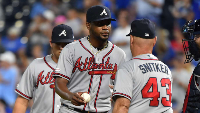 KANSAS CITY, MISSOURI - SEPTEMBER 24:  Starting pitcher Julio Teheran #49 of the Atlanta Braves hands the ball over to manager Brian Snitker #43 as he leaves a game against the Kansas City Royals in the third inning at Kauffman Stadium on September 24, 2019 in Kansas City, Missouri. (Photo by Ed Zurga/Getty Images)