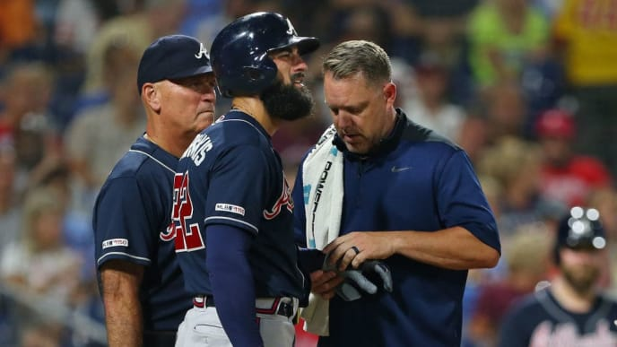 PHILADELPHIA, PA - JULY 26: Nick Markakis #22 of the Atlanta Braves is looked at by a member of the team's medical staff along with manager Brian Snitker #43 after getting hit in the hand by a pitch during the sixth inning of a game against the Philadelphia Phillies at Citizens Bank Park on July 26, 2019 in Philadelphia, Pennsylvania. The Braves defeated the Phillies 9-2. (Photo by Rich Schultz/Getty Images)