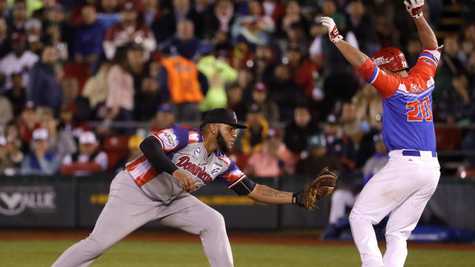 Edwin Espinal (L) of Aguilas Cibaenas of Republica Dominicana takes the ball to put out Johnny Monell (R) of Criollos de Caguas of Puerto Rico during the final of Caribbean Baseball Serie at the Charros Jalisco stadium in Guadalajara, Jalisco State, Mexico, on February 8, 2018 / AFP PHOTO / ULISES RUIZ        (Photo credit should read ULISES RUIZ/AFP via Getty Images)