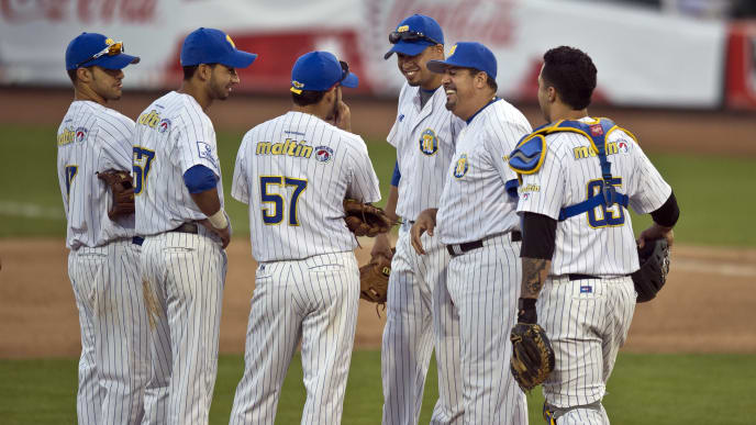 Luis Sojo (C), manager of Magallanes of Venezuela, jokes with his players, in the match against Leones del Escogido of the Dominican Republic, during the 2013 Caribbean baseball series, on February 6, 2013, in Hermosillo, Sonora State, in the northern of Mexico. AFP PHOTO/Ronaldo Schemidt        (Photo credit should read Ronaldo Schemidt/AFP/Getty Images)