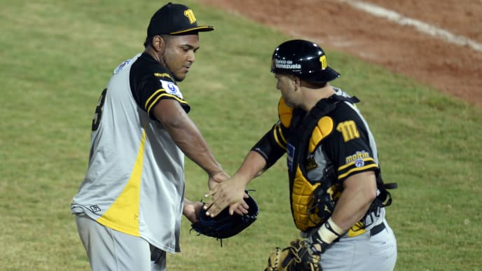 Pitcher Jean Machi (L) and catcher Ramon Hernandez (R) of Venezuela's Navegantes del Magallanes celebrate after defeating Mexico's Naranjeros de Hermosillo during their 2014 Caribbean baseball series game, on February 3, 2014, in Porlamar city, Margarita Island, Nueva Esparta state, Venezuela . AFP PHOTO / LEO RAMIREZ        (Photo credit should read LEO RAMIREZ/AFP/Getty Images)