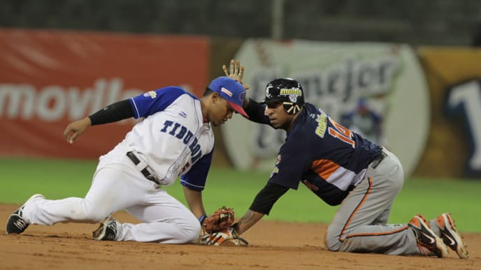 This picture taken on January 16, 2014 shows Venezuelan baseball player Jose Castillo (R) of Caribes de Anzoategui beating the tag at the second base during a baseball game against Tiburones de la Guaira at the Universitario stadium in Caracas. - Four people have been arrested in Venezuela in connection with the deaths of former American big league baseball players Luis Valbuena and Jose Castillo on December 07, 2018. According to police reports stone criminals positioned on the road in a bid to rob the van caused the crash, a common assault strategy in crisis-wracked Venezuela. (Photo by FEDERICO PARRA / AFP)        (Photo credit should read FEDERICO PARRA/AFP via Getty Images)