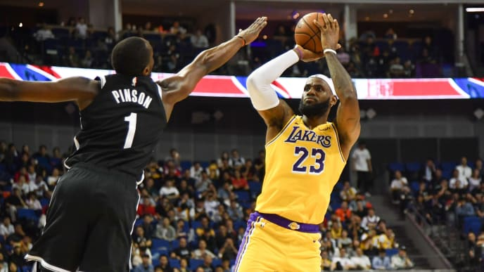 LeBron James of Los Angeles Lakers (R) takes a shot while being guarded by Theo Pinson of the Brooklyn Nets (L) during their National Basketball Association (NBA) pre-season match at the Mercedes Benz Arena in Shanghai on October 10, 2019. (Photo by HECTOR RETAMAL / AFP) (Photo by HECTOR RETAMAL/AFP via Getty Images)