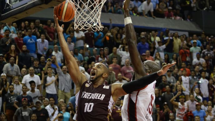 Venezuela's Jose Vargas (L) aims at the basket marked by Canada's Joel Anthony during a FIBA's Americas Qualifier match for the China 2019 Basketball World Cup, at Parque Miranda sport centre in Caracas on November 30, 2018. (Photo by Federico PARRA / AFP)        (Photo credit should read FEDERICO PARRA/AFP/Getty Images)