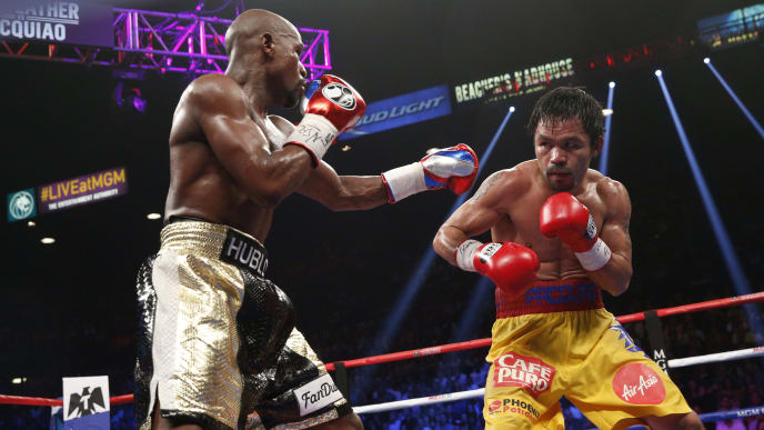 Floyd Mayweather Jr. exchange punches with Manny Pacquiao during their welterweight unification championship bout, May 2, 2015 at MGM Grand Garden Arena in Las Vegas, Nevada.  Mayweather defeated Pacquiao by unanimous decision.  AFP PHOTO / JOHN GURZINKSI        (Photo credit should read JOHN GURZINSKI/AFP via Getty Images)