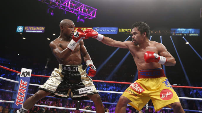 Floyd Mayweather Jr. exchange punches with Manny Pacquiao during their welterweight unification championship bout, May 2, 2015 at MGM Grand Garden Arena in Las Vegas, Nevada.  Mayweather defeated Pacquiao by unanimous decision.  AFP PHOTO / JOHN GURZINKSI        (Photo credit should read JOHN GURZINSKI/AFP/Getty Images)