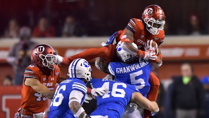 SALT LAKE CITY, UT - NOVEMBER 24: Dayan Ghanwoloku #5 of the Brigham Young Cougars tackles the leaping TJ Green #4 of the Utah Utes in the second half of a game at Rice-Eccles Stadium on November 24, 2018 in Salt Lake City, Utah. (Photo by Gene Sweeney Jr/Getty Images)