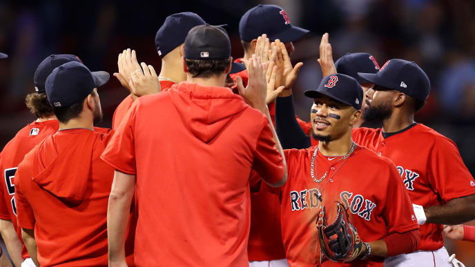 BOSTON, MASSACHUSETTS - AUGUST 17: Mookie Betts #50 of the Boston Red Sox celebrates with teammates after the Red Sox defeat the Orioles 4-0 at Fenway Park on August 17, 2019 in Boston, Massachusetts.  (Photo by Maddie Meyer/Getty Images)